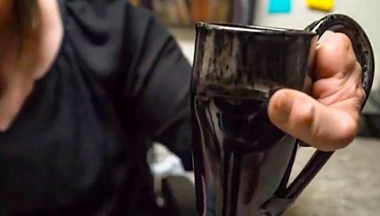 Closeup of Jenny's hand holding a custom mug